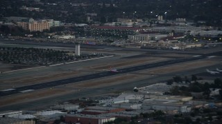 AX0162_117 - 8K stock footage aerial video of a commercial airplane taking off at twilight from Burbank Airport, California