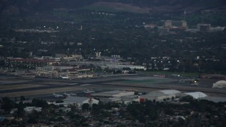 AX0162_118 - 8K stock footage aerial video of a commercial airplane soaring away from Burbank Airport, California at twilight