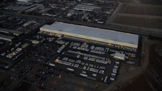 AX0162_119 - 8K stock footage aerial video approaching and passing a large warehouse building in Pacoima, California at twilight