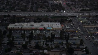 AX0162_120 - 8K stock footage aerial video of Pacoima Center shopping center in Pacoima, California at twilight