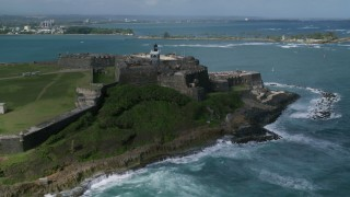 AX101_012 - Aerial stock footage of 5k Aerial Video of a Historic fort along the coast with clear blue water, Old San Juan Puerto Rico