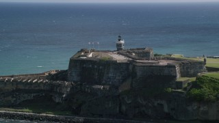 AX101_016 - Aerial stock footage of 5k Aerial Video of a Historic fort along the coast resting on clear blue water, Old San Juan Puerto Rico