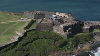AX101_026 - Aerial stock footage of 5k Aerial Video Flyover historic fort and lighthouse along blue waters, Old San Juan Puerto Rico
