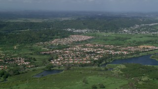 AX101_033 - Aerial stock footage of 5k Aerial Video of Residential neighborhoods among trees and grassy areas, Dorado, Puerto Rico