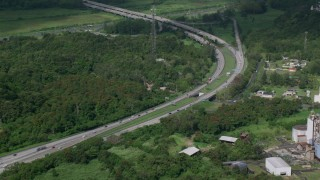 AX101_036 - Aerial stock footage of 5k Aerial Video of a Highway cutting through rural area of grass and trees, Vega Alta, Puerto Rico Day