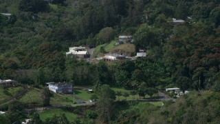 AX101_042 - Aerial stock footage of 5k Aerial Video of Tree covered hills with rural homes, Vega Baja, Puerto Rico