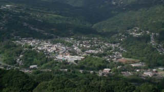AX101_046 - Aerial stock footage of 5k Aerial Video of a Town nestled in a valley of trees, Ciales, Puerto Rico