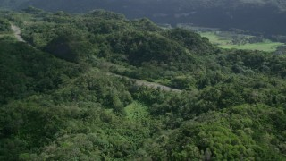AX101_076 - 5k stock footage aerial video of a Highway cutting through lush green forests, Karst Forest, Puerto Rico