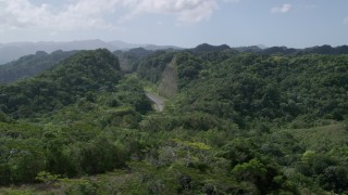 AX101_078 - 5k stock footage aerial video of Light traffic cutting through lush green mountains, Karst Forest, Puerto Rico