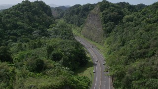 AX101_080 - 5k stock footage aerial video of a Highway through lush green mountains, Karst Forest, Puerto Rico