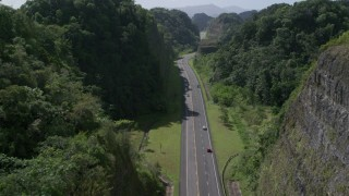 AX101_081 - 5k stock footage aerial video Following traffic along a highway through lush green mountains, Karst Forest, Puerto Rico
