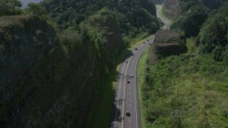 AX101_082 - 5k stock footage aerial video Following light traffic through lush green mountains, Karst Forest, Puerto Rico