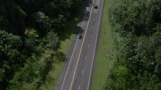 AX101_083 - 5k stock footage aerial video Tilting up on a highway through lush green mountains, Karst Forest, Puerto Rico