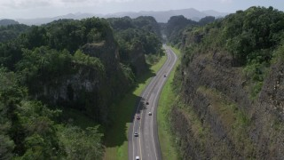 AX101_084 - 5k stock footage aerial video of Light traffic on a highway through lush green mountains, Karst Forest, Puerto Rico