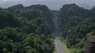AX101_085 - 5k stock footage aerial video Flying above highway cutting through lush green mountains, Karst Forest, Puerto Rico