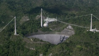AX101_090 - 5k stock footage aerial video revealing Arecibo Observatory among lush green forests, Puerto Rico
