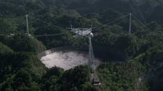 AX101_097 - 5k stock footage aerial video of Arecibo Observatory surrounded by trees, Puerto Rico
