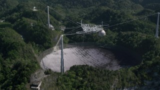 AX101_098 - 5k stock footage aerial video of Arecibo Observatory surrounded by trees, Puerto Rico
