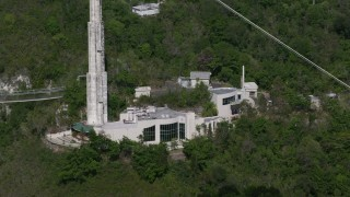 AX101_102 - 5k stock footage aerial video of Arecibo Observatory building set among trees, Puerto Rico