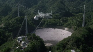 AX101_105 - 5k stock footage aerial video Orbiting Arecibo Observatory among the trees, Puerto Rico