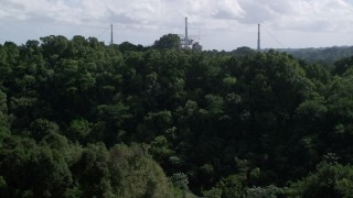 AX101_109 - 5k stock footage aerial video Descending toward lush jungle from Arecibo Observatory, Puerto Rico