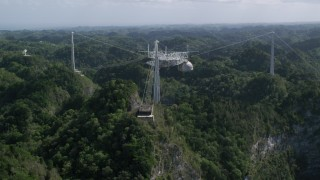 AX101_111 - 5k stock footage aerial video Tilting down on Arecibo Observatory surrounded by trees, Puerto Rico