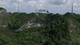 AX101_114 - 5k stock footage aerial video Approaching tree filled hillside toward Arecibo Observatory, Puerto Rico