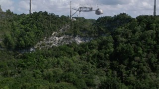AX101_115 - 5k stock footage aerial video Low approach above trees toward Arecibo Observatory, Puerto Rico