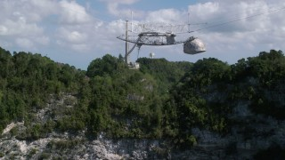 AX101_116 - 5k stock footage aerial video tilt down on Arecibo Observatory nestled in the trees, Puerto Rico