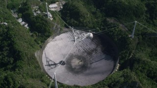 AX101_120 - 5k stock footage aerial video Hovering above Arecibo Observatory and surrounding trees, Puerto Rico