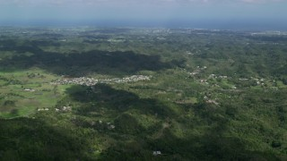 AX101_124 - 5k stock footage aerial video of Rural homes situated among lush green trees in Karst mountains, Arecibo, Puerto Rico