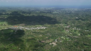 AX101_125 - 5k stock footage aerial video of Rural homes among tree covered karst mountains, Arecibo, Puerto Rico Day Partly Cloudy Side View