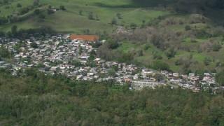 AX101_127 - 5k stock footage aerial video of Rural neighborhood surrounded by trees, Arecibo, Puerto Rico
