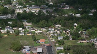 AX101_131 - 5k stock footage aerial video of Rural neighborhood with trees, Arecibo, Puerto Rico