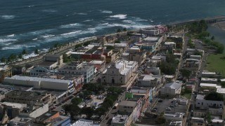 AX101_138 - 5k stock footage aerial video of Coastal buildings and tilt down on Catedral San Felipe, Arecibo Puerto Rico