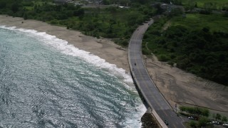 AX101_140 - 5k stock footage aerial video of a Coastal road cutting through trees and over a beach along blue water, Arecibo, Puerto Rico