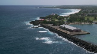 AX101_142 - 5k stock footage aerial video of the Arecibo Lighthouse along the blue waters of the Caribbean, Puerto Rico