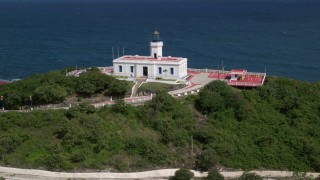 AX101_145 - 5k stock footage aerial video of the Arecibo Lighthouse along the coast and clear blue Caribbean waters, Puerto Rico