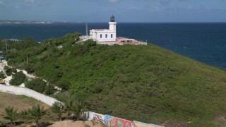 AX101_146 - 5k stock footage aerial video of the Arecibo Lighthouse along the coast and blue Caribbean waters, Puerto Rico