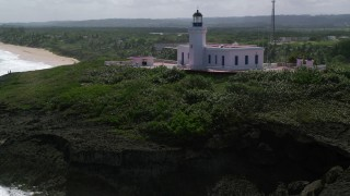 AX101_149 - 5k stock footage aerial video flying over Arecibo Lighthouse along the coast, Puerto Rico
