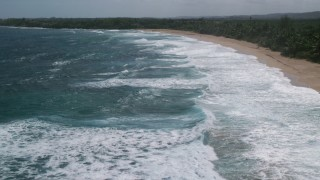 AX101_150 - 5k stock footage aerial video Flying low over clear blue waters along a beach, Arecibo, Puerto Rico