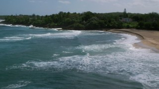 AX101_152 - Aerial stock footage of Clear blue waters next to a tree lined coast, Arecibo, Puerto Rico