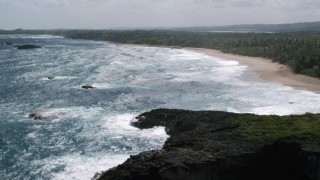 AX101_155 - 5k stock footage aerial video Flying over blue waters toward the beach and tree lined coast, Arecibo, Puerto Rico