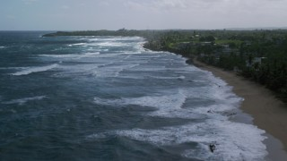 AX101_157 - 5k stock footage aerial video Flying over blue water along the coast and oceanfront property, Arecibo, Puerto Rico