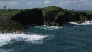 AX101_162 - 5k stock footage aerial video of Rock formations along the coast of clear blue water, Arecibo, Puerto Rico