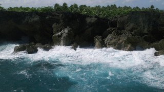 AX101_163 - 5k stock footage aerial video of Coastal rock formations and caves on clear blue water, Arecibo, Puerto Rico