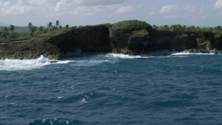 AX101_165 - 5k stock footage aerial video of Rock formations on the coast of crystal blue water, Arecibo, Puerto Rico