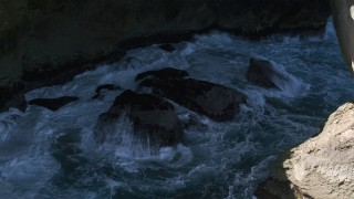 AX101_167 - 5k stock footage aerial video of Churning water in a sea cave, Arecibo, Puerto Rico