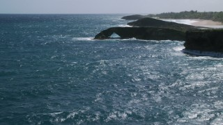 AX101_168 - 5k stock footage aerial video of an Arched rock formation in crystal blue water, Arecibo, Puerto Rico