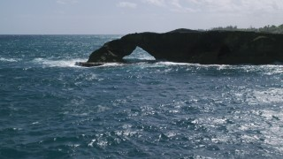 AX101_169 - 5k stock footage aerial video of an Arched rock formation in crystal blue waters, Arecibo, Puerto Rico